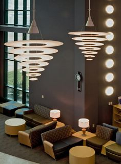 Dramatic pendant light fixtures by Louis Poulsen are a major design feature as are the vertical disks of light flanking the exterior window wall.
