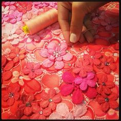 """Final adjustments being made to the red / pink hand dyed, beaded lace in the Matthew Williamson design studio before London fashion week. """"Final adjustments... Hand-dyed, hand-cut, hand-beaded lace #LFW #CatwalkCountdown #BehindTheSeams"""""""