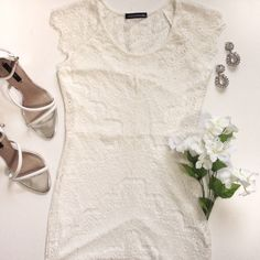 NWOT White Lace Bodycon Dress White lace perfection. This darling yet sexy dress comes in white lace and features scalloped sleeves and hem, a bodycon silhouette and enclosed zipper at side. NWOT, excellent condition. Partially lined. 65% cotton, 35% nylon. Lining is 100% polyester. Dresses
