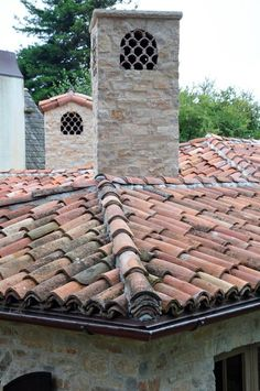 close up roof tiles and stone chimney Stone Chimney, Chimney Cap, Spanish Tile Roof, Chimney Decor, Wood Arbor, Clay Roof Tiles, Roof Edge, Brick Arch, Wood Garage Doors