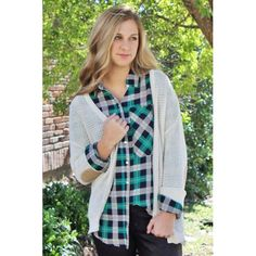 Our Patch Me Up Cardigan features tan suede elbow patches on a cozy cream knit. This sweater can button up the front. Shown here with our Kelly Plaid Button-Up. Our model Olivia is shown wearing a size medium.