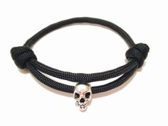 This handmade Silver Skull Bracelet is made with Black Paracord 550 and a Metal Silver Skull Bead. The bracelet is adjustable and is available in