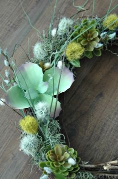 Faux succulents and Spring flower picks from the Dollar Store come together to create a beautiful and inexpensive Spring Wreath.