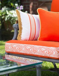 Orange outdoor cushions with braids and trimmings from the Saison collection by Samuel and Sons Passementerie