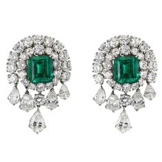 VAN CLEEF & ARPELSEach of these magnificent Van Cleef & Arpels earrings features a large, center emerald-cut emerald surrounded by round-cut diamonds, with dangling pear-shaped diamonds adding drama to the 18K white gold setting. Accompanied by certificates stating that the emeralds are Colombian, and untreated.Circa 1990s