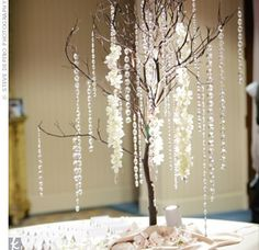 Strands of orchids and crystals hanging from manzanita branches highlighted the seating assignments. On the table, more orchids and crystals dressed up the simple, tented cards.-- pretty