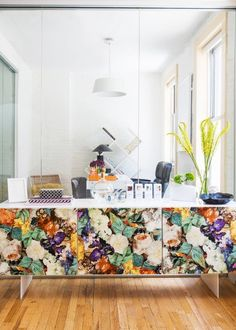 Conference room with bold floral credenza, wood floors, and glass walls