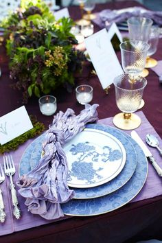 Antique flatware with mother-of-pearl handles flank gold-trimmed lavender porcelain. An assemblage of randomly-placed clear tealight holders imbue elegance to the outdoor setting.