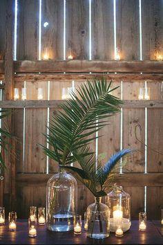 Decoração simples em estilo rústico com folhas de palmeira em vidros transparentes. #casamento #decoração #folhagem
