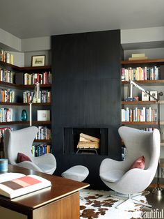 """""""The attitude of the library is modern, but it's cozy and warm — almost womblike,"""" architect David Mann says of this space in a New York City apartment. Walls are painted Ralph Lauren Orion Grey. Mix Table lamp from Luceplan.   - HouseBeautiful.com"""