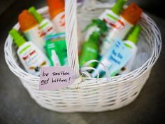 Guests are provided with a basket of bug spray at an outdoor wedding