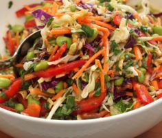 ASIAN SLAW RECIPE: Take a look at my recipe for a delicious and very flavorful Asian slaw, where the slaw is made from shredded green and red cabbage, grated carrots, scallions, red bell pepper, edamame and fresh cilantro. The dressing is then made from peanut butter, sesame oil, vegetable oil, rice vinegar, soy sauce, brown sugar, garlic and ginger all whisked together. The dressing is then added to the slaw and your Asian slaw is tossed until combined.