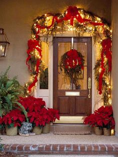 Dress up a boring doorway with a red/ green color scheme.  Door outlined with garland, glowing lights, and red bows complements the hanging wreath. A grouping of poinsettia plants adds the perfect punch of holiday cheer. #RecipeIdea