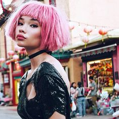 Ashley Moore in a short pink choppy wig and black sequin dress