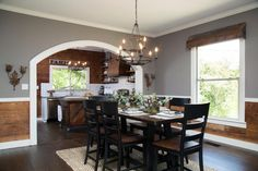 Chip and Joanna expanded the kitchen entryway by cutting a wide archway, making both the kitchen and the dining room feel larger. Twin modern-industrial style chandeliers illuminate the kitchen island and dining table.