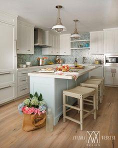 Beautiful white and blue cottage kitchen is equipped with a stunning pale blue kitchen island topped with a white marble countertop seating three tan backless counter stools illuminated by two industrial pendant lights.