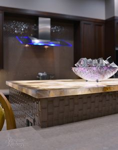 Three-tier center island with mini glass tile has back lit semi-precious stone counter top from Zicana.