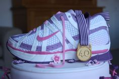 I made this ladies running shoe / trainer cake for my friend's 40th birthday. The cake is based on my Nike Air Pegasus trainers, with the colours changed to pink, purple and white (and not covered in mud!), with a sugar paste gold medal draped across it. Biggest compliment was when a couple of people at the party asked me if it was a real trainer. Running and cakes. Two of my favourite things :-)