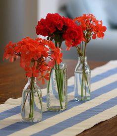 Red Geranium flowers in little glass bottles on my new cornflower blue table runner by Lilibet Stanley