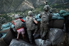 """Soldiers from the U.S. Army First Battalion, 26th Infantry take defensive positions at firebase Restrepo after receiving fire from Taliban positions in the Korengal Valley of Afghanistan's Kunar Province, in this May 11, 2009 file photo. Spc. Zachery Boyd of Fort Worth, TX, far left was wearing """"I love NY"""" boxer shorts after rushing from his sleeping quarters to join his fellow platoon members. From far right is Spc. Cecil Montgomery of Many, LA and Jordan Custer of Spokane, WA, center. (AP P..."""