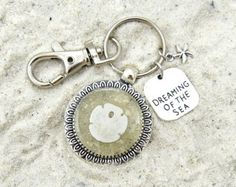 This seashell keychain captures the magic of the ocean so that you can bring the beach wherever you go. Florida sand and a real sand dollar