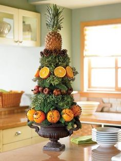 Pineapple tower: Slice the point of a floral foam cone to make base for pineapple later on. Build from bottom up. Use floral picks to attach fruit and pinecones, Push end of greenery into foam. All Things Christmas, Christmas Holidays, Christmas Crafts, Xmas, Christmas Topiary, Outdoor Christmas, Fruit Decorations, Decoration Table, Stage Decorations