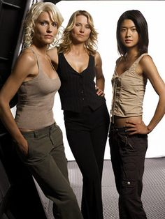 CAPRICA SIX, SHARON ''BOOMER'' AGATHON, AND D'ANNA BIERS (Tricia Helfer, Grace Park, and Lucy Lawless) in Battlestar Galactica (2004-present) Cerebral villainy just doesn't get any…