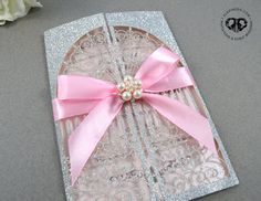Elegant silver glitter, pink and blush pink laser cut invitation. Pink satin ribbon bow and flower pearl rhinestone embellishment. Fancy, classy, vintage, modern, beautiful. Wedding, Quinceañera, sweet 16, bridal shower, birthday party. Custom. Vintage door