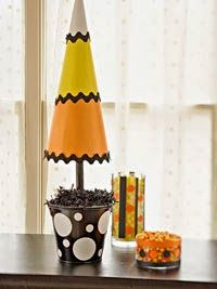 Candy Corn Inspired DIY Topiary craft from Better Homes & Gardens.  Cute Halloween decorations when you add in the black rick rack & black pail.