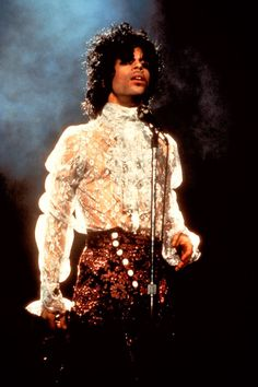 Prince is as regal as ever in a frilly white blouse during the Purple Rain tour in 1984. (There are many other great ruffle moments from his sartorial history, but this one — with sparkly high-waisted pants — feels particularly memorable to us.) #refinery29 http://www.refinery29.com/2016/04/108919/prince-fashion-outfits-style#slide-2