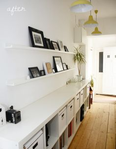 Hallway storage using Ikea Expedit shelves.  Picture wall using Ikea picture shelves. Yellow vintage style ceiling lights.