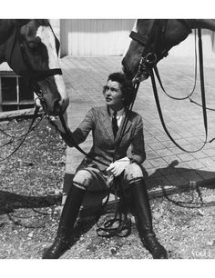 Mary Goetchius, wearing a checked cotton riding jacket, jodhpurs, and black, knee-high riding boots, sitting on a tiled terrace and holding the reins of two horses.  Photo by Toni Frissell.  Vogue, July 1938.