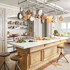 In the kitchen, interior designer Rocky Rochon softened the impact of workhorse appliances with pieces seasoned with character: a custom china cabinet and an antique French patisserie table repurposed as the kitchen island. | Coastalliving.com
