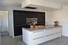 Wit gelakt keukeneiland met zwart geborsteld eiken kastenwand en een composiet blad in beton look. De hoge kasten hebben een gestucte ombouw