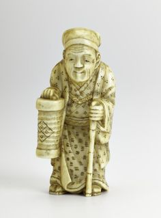 Netsuke of carved ivory, man with a paper lantern and a stick, signed: Japan, by Tomotsugu