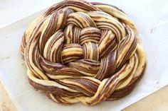 Un desert fabulos cu gust intens de ciocolată.  INGREDIENTE: Pentru aluat: -500 gr de făină; -100 gr de zahăr; -1 linguriță de sare; -1 lingură de drojdie uscată sau 25 gr de drojdie proaspătă; -2 ouă; -100 gr de unt moale tăiat cuburi; -120 ml de lapte la temperatura camerei. Pentru umplutură: -120 gr de ciocolată neagră; -100 gr de unt; -60 gr de zahăr; -1 lingură de cacao; -100 gr de migdale măcinate pudră. Pentru glazură: -50 gr de zahăr; -60 ml de apă sau suc de portocală. MOD DE…