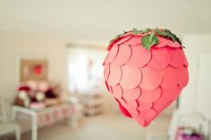 Strawberry hanging decoration. Looks like an upside-down balloon covered in red paper circles and real strawberry plant leaves.