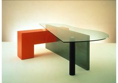 Bernini Desk 1998 - Each part of this desk has its proper function, apparently unrelated to each other as form. The red L shaped element is a file cabinet on one side and a bar on the other side of the gray modesty panel. The black tube is just a supporting leg and the piano shaped top is glass, to reveal the play of the desk components.