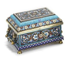 A silver-gilt and cloisonné enamel casket Nikolai Vasilevich Alexeev, Moscow, circa 1895 shaped rectangular with stepped hinged lid, the surface enriched with stylized foliate motifs against stippled ground within beaded borders, flanked by two swing handles and raised upon four bell-shaped feet, with key, 84 standard width including handles
