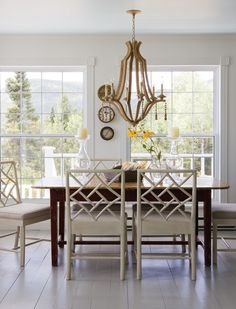 Chic Dining Room with cream color walls and wood framed chairs is dressed up by the intricate wood chandelier.  The large window allow lots of light into the room giving it a bright, airy effect.
