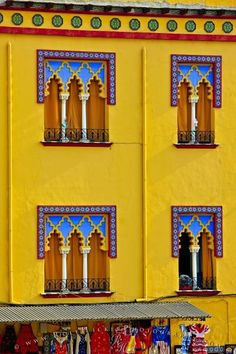 Plenty of typical moorish architecture can be found in the city of Cordoba, this outside facade shows colorful windows near the Mezquita.  Spain
