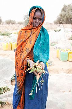 Woman shows the carrots she gathered from the Women's garden. Photo credit: David Orme.