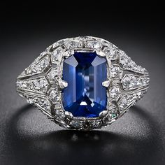 An elegant, elongated emerald-cut Ceylon sapphire radiates from atop a magnificently ornamented platinum and diamond mounting in this rare and wonderful original Art Deco jewel, circa 1925. The beautiful 2.50 carat sapphire glistens from within a distinctive diamond-set honeycomb-style frame which artfully transitions into dramatic sparkling fan-motif shoulders. Superb and stunning original Art Deco sapphire and diamond rings of this caliber do not come around very often.
