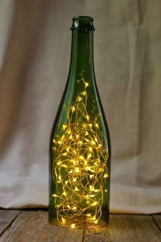 This beautiful wine bottle light is perfect for brightening centerpieces and table decor. Looks great with warm white fairy lights. Good for weddings, events and home decor. #winebottlelights #fairylights #tabledecor