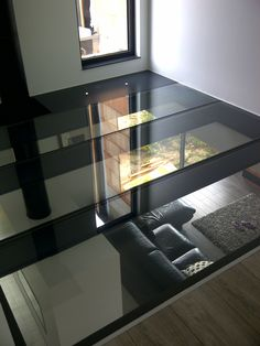 Continuous sections of glass flooring panels moving light and sight between floor levels