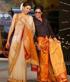 Deepika Padukone looked stunning in a sheer gold sari, while Shah Rukh Khan donned an orange lungi paired with a black shirt. #Bollywood #Fashion