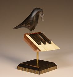 """Raven on 7 Piano Keys,"" hand-carved and painted wooden raven on seven vintage wooden piano keys on a hand-painted wooden base. By Mark Orr."
