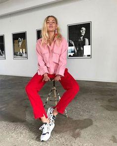 Combinação de cores vibrantes com camisa rosa, calça cropped vermelha e tênis branco.