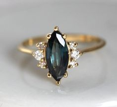 Naomi Deep Teal Sapphire Ring, Blue Green Sapphire Engagement Ring Yellow Gold Naomi ring is a. Green Sapphire Engagement Ring, Delicate Engagement Ring, Yellow Engagement Rings, Deco Engagement Ring, Blue Sapphire Rings, Blue Rings, Vintage Engagement Rings, Yellow Gold Rings, Blue And White Rings