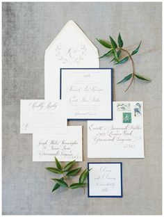 Wedding invitation suite with a wreath monogram envelope liner and navy blue edges by Paper Tangent. Image by Rachel May Photography.